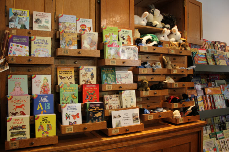 Sticker books and stuffed animals displayed in cabinet